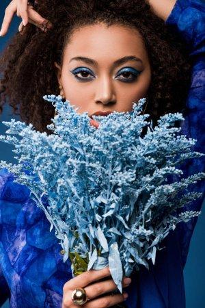 afrikanisch-amerikanische Frau mit Make-up hält Strauß isoliert auf blau