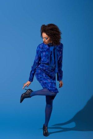Photo pour Attrayant afro-américain femme en robe toucher ses chaussures sur fond bleu - image libre de droit