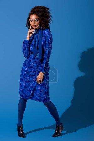 Photo pour Attrayant afro-américain femme en robe sur fond bleu - image libre de droit