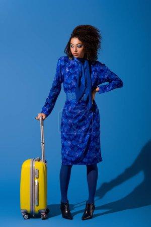 Photo pour Femme afro-américaine avec la main sur la hanche tenant sac de voyage sur fond bleu - image libre de droit