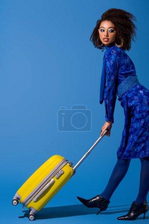Photo pour Africaine américaine femme tenant sac de voyage sur fond bleu - image libre de droit