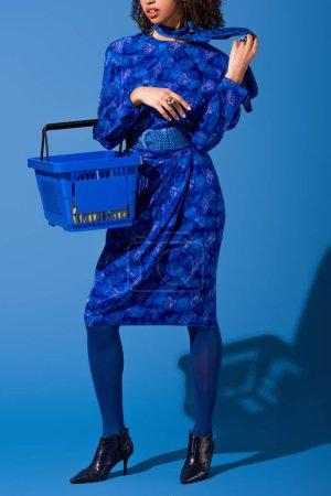 Photo pour Vue recadrée de femme afro-américaine tenant panier sur fond bleu - image libre de droit
