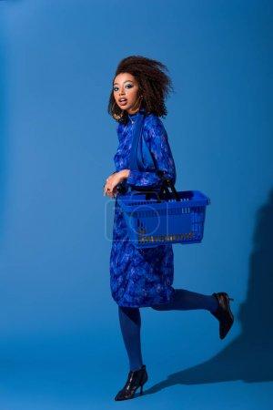 Photo pour Afro-américaine femme tenant panier sur fond bleu - image libre de droit