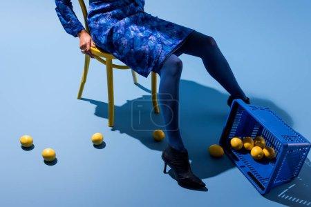 Photo pour Vue recadrée de femme afro-américaine assise sur une chaise sur fond bleu - image libre de droit