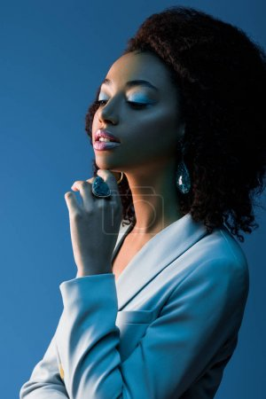 Photo for African american woman in jacket looking away isolated on blue - Royalty Free Image