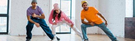 Photo pour Plan panoramique d'hommes et de femmes multiculturels élégants breakdance - image libre de droit