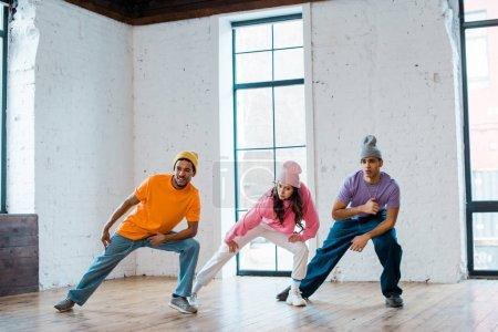 elegantes hombres y chicas multiculturales en sombreros breakdance