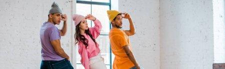 plano panorámico de jóvenes bailarines multiculturales tocando sombreros mientras bailan breakdance