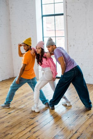 Photo for Multicultural dancers in hats posing while breakdancing - Royalty Free Image