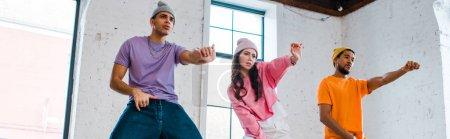 Panoramaaufnahme von multikulturellen Männern, die beim Breakdance mit attraktiven Mädchen gestikulieren