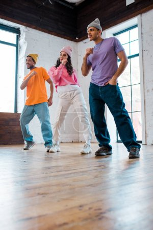 handsome multicultural men in hats breakdancing with attractive girl