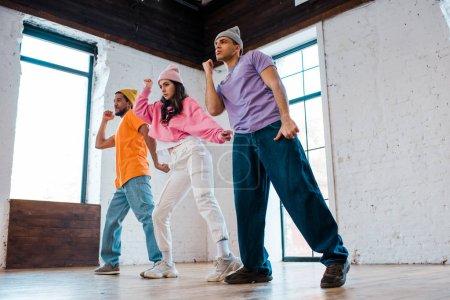 gutaussehende multikulturelle Männer in Hüten Breakdance mit schönen Mädchen