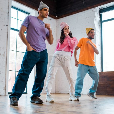 stylish multicultural men in hats breakdancing with beautiful girl