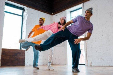 stilvolle multikulturelle Männer in Hüten Breakdance mit schöner Frau