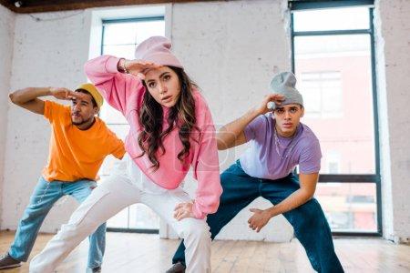 enfoque selectivo de la chica elegante breakdance con hombres multiculturales en sombreros