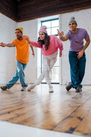 fille élégante gestuelle tout en breakdance avec des hommes multiculturels heureux en chapeaux
