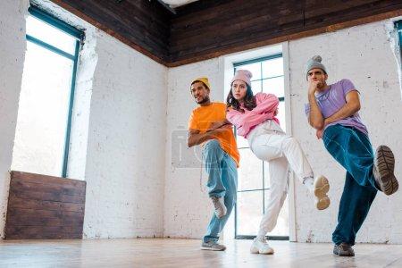 fille élégante avec des bras croisés breakdance avec des hommes multiculturels dans des chapeaux