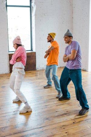 chica atractiva con brazos cruzados breakdancing con elegantes hombres multiculturales en sombreros