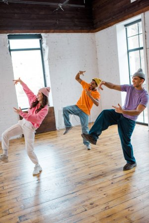 Photo for Attractive girl breakdancing and gesturing with stylish multicultural men in hats - Royalty Free Image