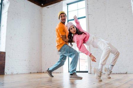 attrayant fille breakdance près afro-américain homme en chapeau