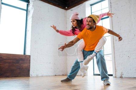 alegre africano americano hombre piggybacking atractiva bailarina