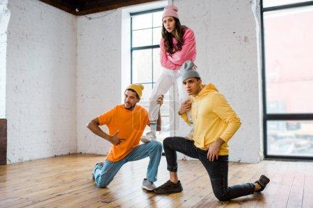 Photo pour Des hommes multiculturels en chapeaux tenant une belle danseuse aux bras croisés - image libre de droit