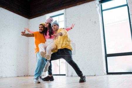 Photo pour Hommes multiculturels en chapeaux tenant une danseuse attrayante - image libre de droit