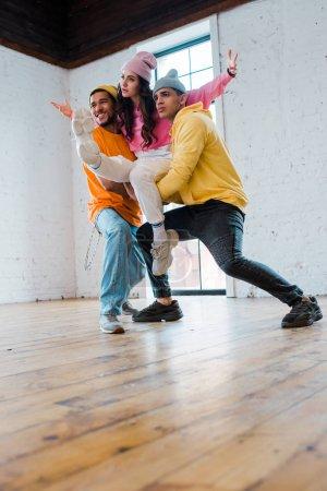 Photo pour Hommes multiculturels stylisés en chapeaux tenant une danseuse attrayante - image libre de droit