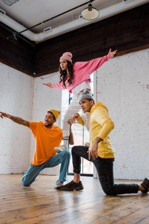 Photo pour Hommes multiculturels en chapeaux tenant des danseurs de style avec des mains tendues - image libre de droit
