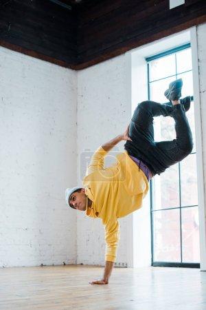 trendy man in hat breakdancing in dance studio