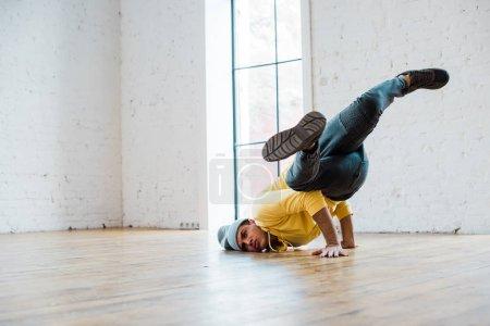 young man in hat breakdancing in dance studio