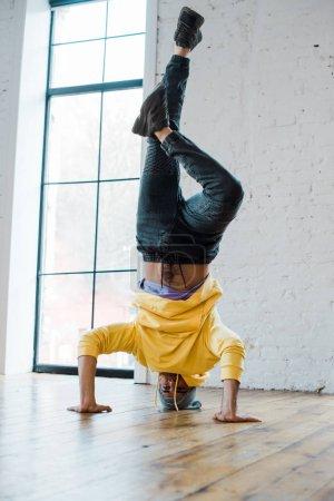 Stylischer Mann mit Hut macht Handstand beim Breakdance im Tanzstudio