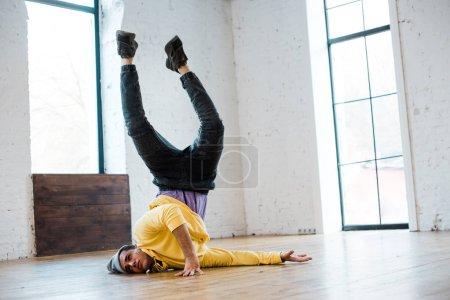 Photo pour Homme au chapeau breakdance sur le sol en studio de danse - image libre de droit