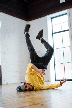 handsome man in hat breakdancing on floor in dance studio