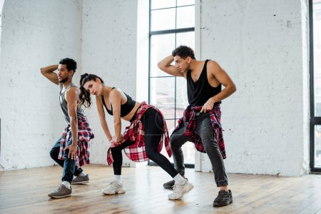 Photo for Multicultural men and woman dancing jazz funk in dance studio - Royalty Free Image