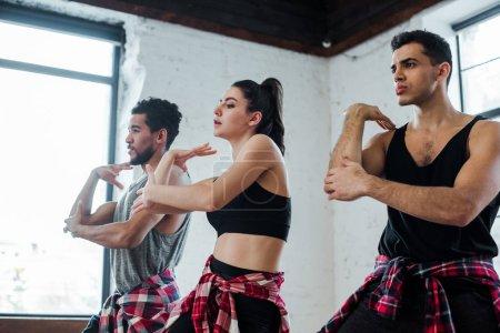 Photo pour Beaux hommes multiculturels et belle jeune femme dansant jazz funk - image libre de droit