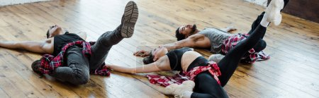 Photo for Panoramic shot of multicultural men and attractive woman lying on floor while dancing jazz funk - Royalty Free Image
