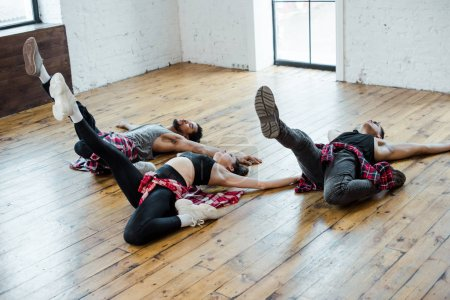 Photo for Multicultural men and attractive woman lying on floor while dancing jazz funk - Royalty Free Image