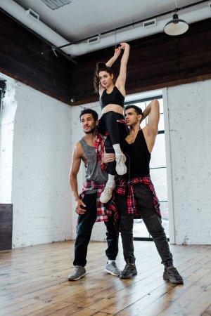 Photo pour Des hommes multiculturels forts tenant une femme séduisante en posant dans un studio de danse - image libre de droit