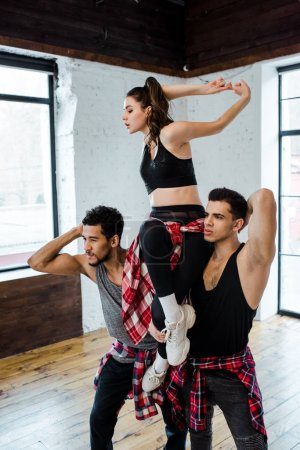Photo pour Des hommes multiculturels forts tenant une fille séduisante en posant dans un studio de danse - image libre de droit
