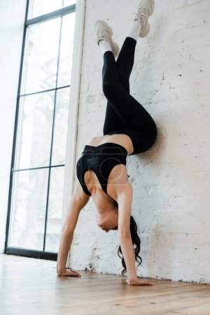 Photo pour Un jeune danseur fait un pied à main près d'un mur de brique dans un studio de danse - image libre de droit