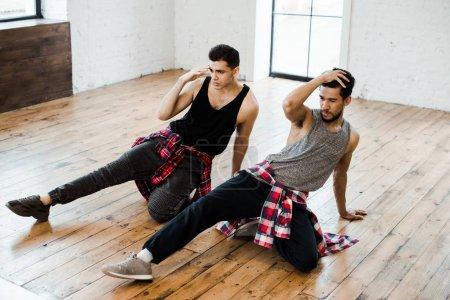 Photo pour Danseurs multiculturels se touchant les cheveux en dansant jazz funk dans un studio de danse - image libre de droit