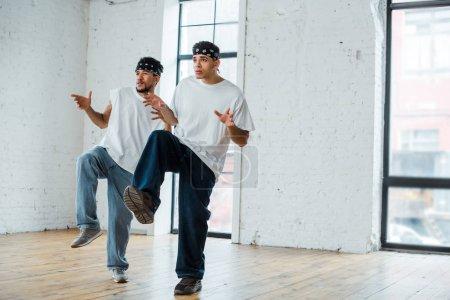 Photo pour Jeunes danseurs multiculturels dans des bandeaux dansant hip-hop - image libre de droit