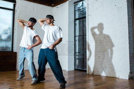 Photo pour Pleins feux sur de beaux danseurs multiculturels en bandeau posant dans un studio de danse - image libre de droit