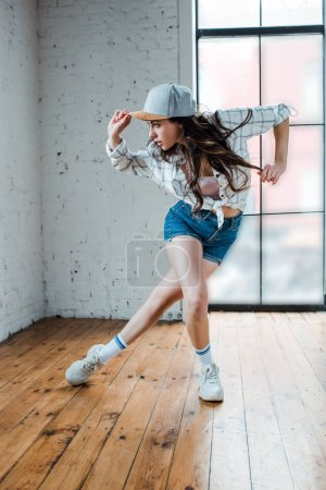 young woman in denim shorts touching cap and dancing hip-hop