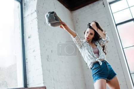 beautiful dancer holding cap and touching hair in dance studio