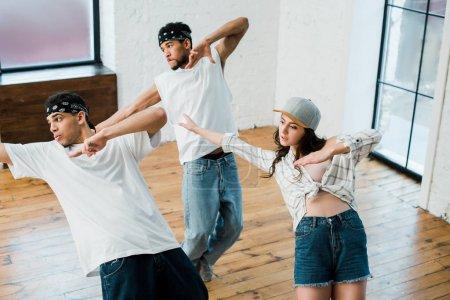 Photo pour Danseurs multiculturels en train de danser le hip-hop dans un studio de danse - image libre de droit