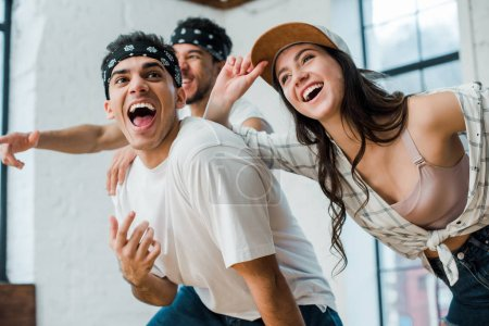 selective focus of cheerful multicultural dancers laughing in dance studio