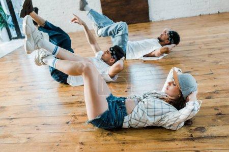 selective focus of trendy girl in cap lying on floor with multicultural dancers in dance studio