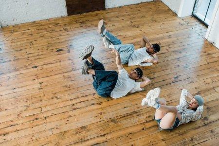 vista aérea de chica de moda tumbada en el suelo con bailarines multiculturales mientras bailan breakdance en el estudio de baile
